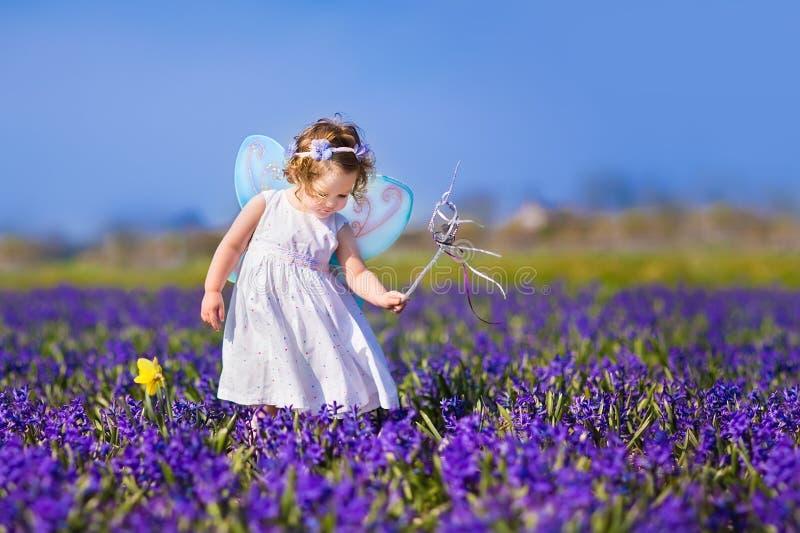 Милая девушка малыша в fairy костюме в поле цветка стоковые фотографии rf