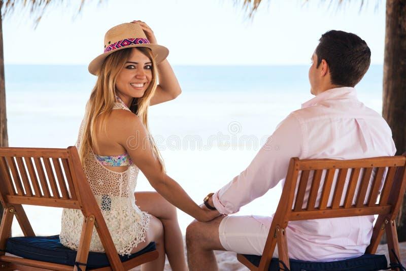 Милая девушка на пляже с ее парнем стоковая фотография