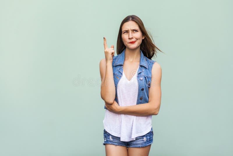 Милая девушка непринужденного стиля с веснушками получила идею и она подняла ее палец вверх и думать стоковые фото