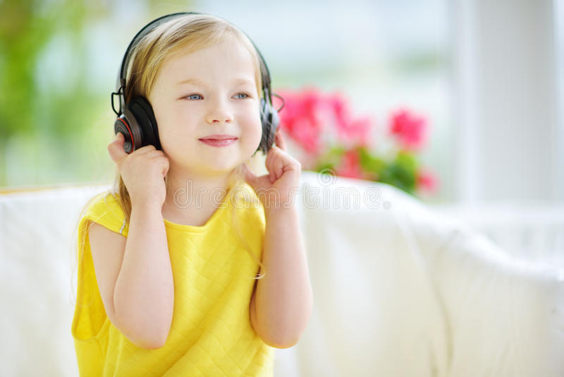 Милая девушка нося огромные беспроволочные наушники Милый ребенок слушая к музыке Школьница имея потеху слушая к песням ` s ребен стоковая фотография rf