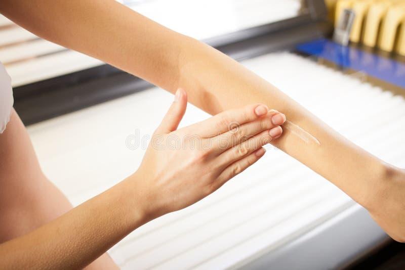 Милая девушка обрабатывает ее кожу перед загорать стоковое фото rf