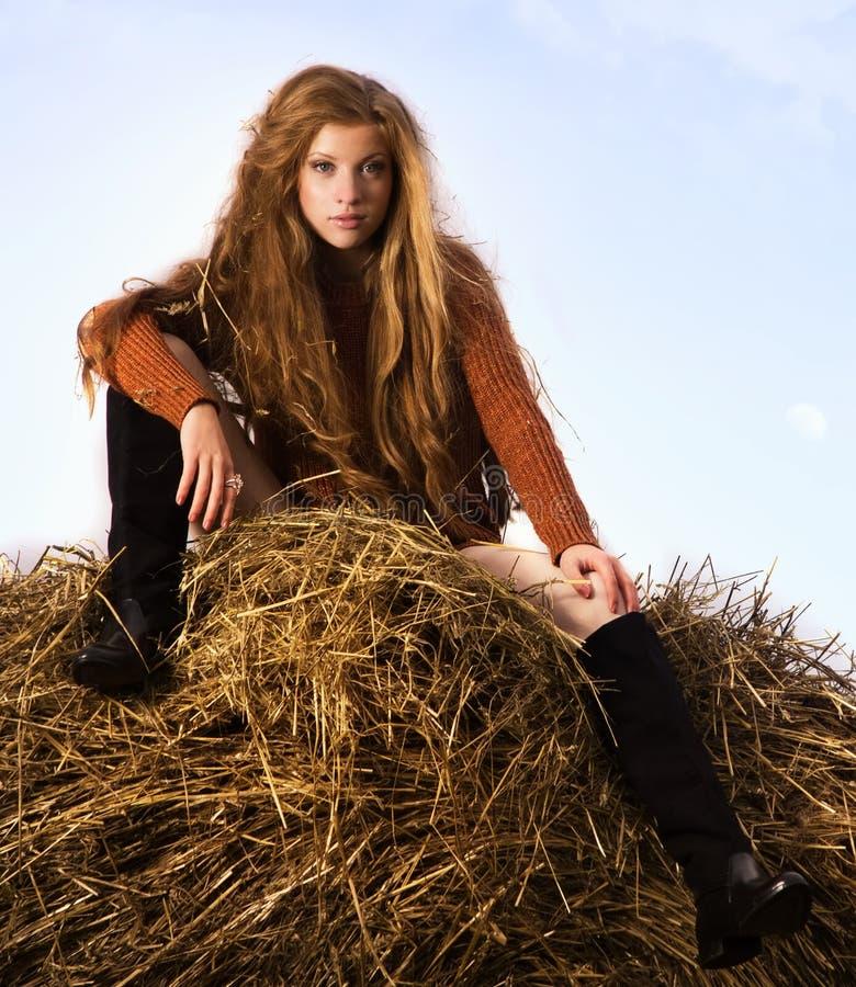 Милая девушка отдыхая на связке соломы стоковая фотография