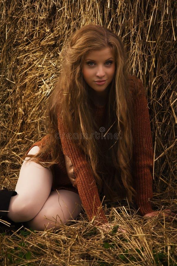 Милая девушка отдыхая на связке соломы стоковое фото