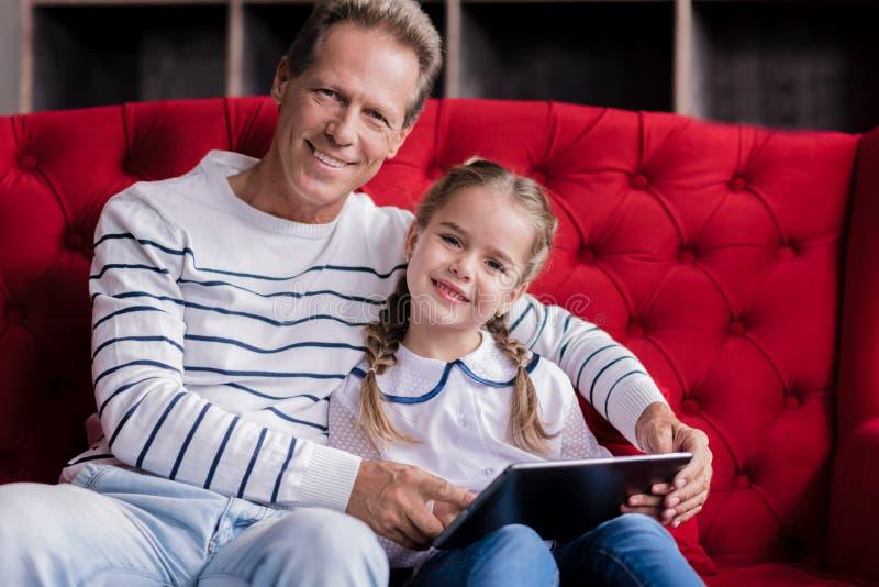 Милая девушка отдыхая с ее дедом и держа таблетку стоковая фотография rf