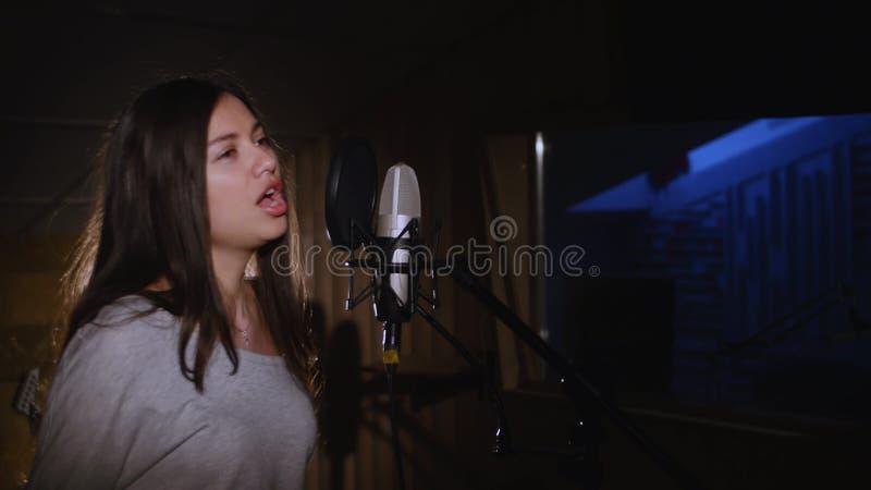 Милая девушка поя в микрофон студии Девушка носит наушники на белой предпосылке В нижнем свете  стоковое изображение rf