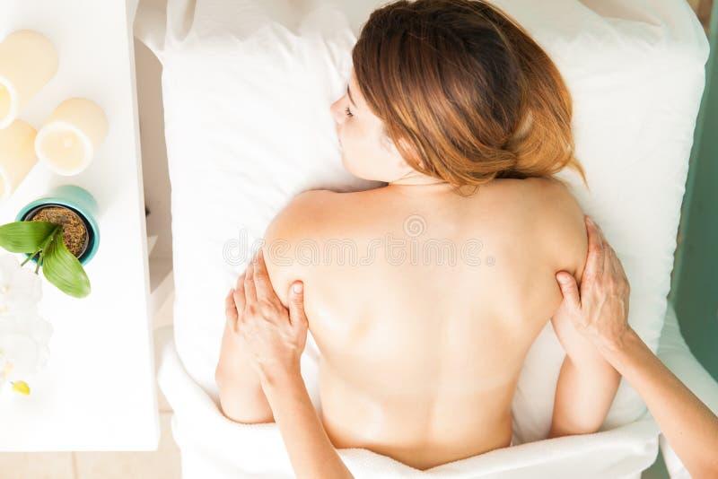 Милая девушка получая задний массаж стоковое изображение