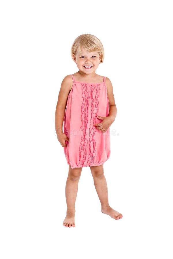 Милая девушка представляя для камеры, в розовом коротком платье стоковая фотография rf
