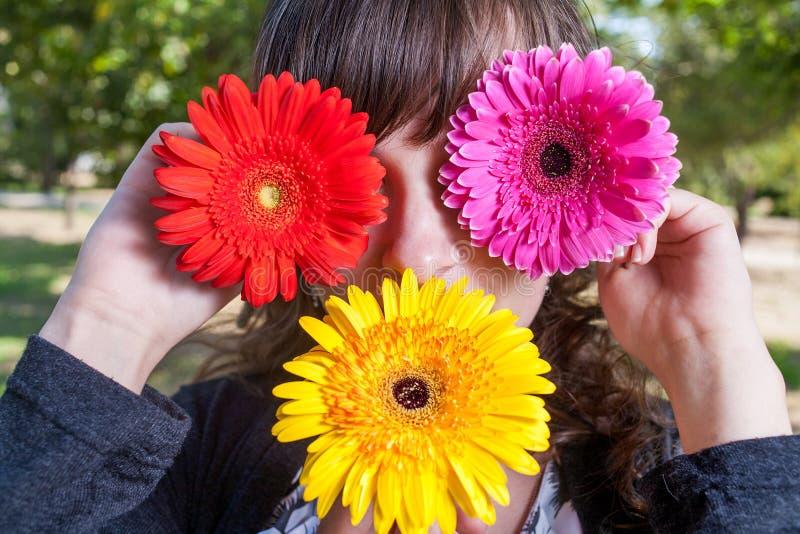 Милая девушка прячет ее глаза и рот цветками gerbera стоковые изображения