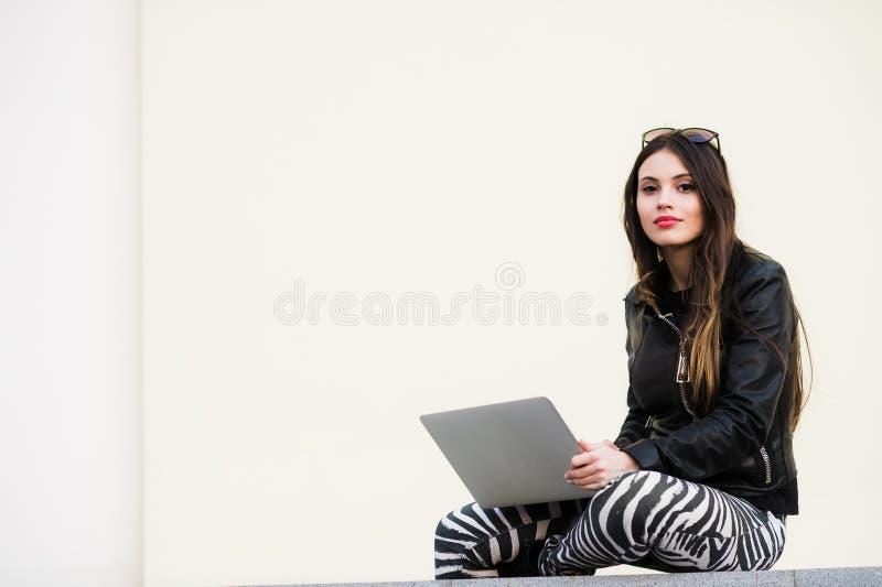 Милая девушка работая при компьтер-книжка сидя на бетонной стене outdoors на университетском кампусе стоковое фото rf