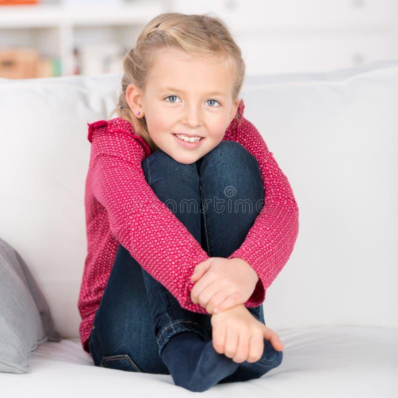 Милая девушка сидя на софе стоковые изображения