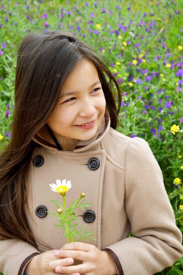 Милая девушка ся держащ цветок стоковая фотография rf