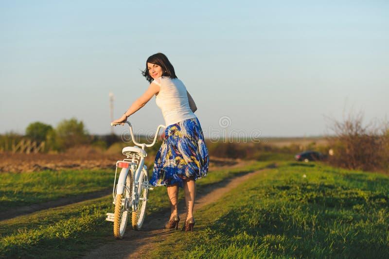 Милая девушка с белым велосипедом стоковое фото