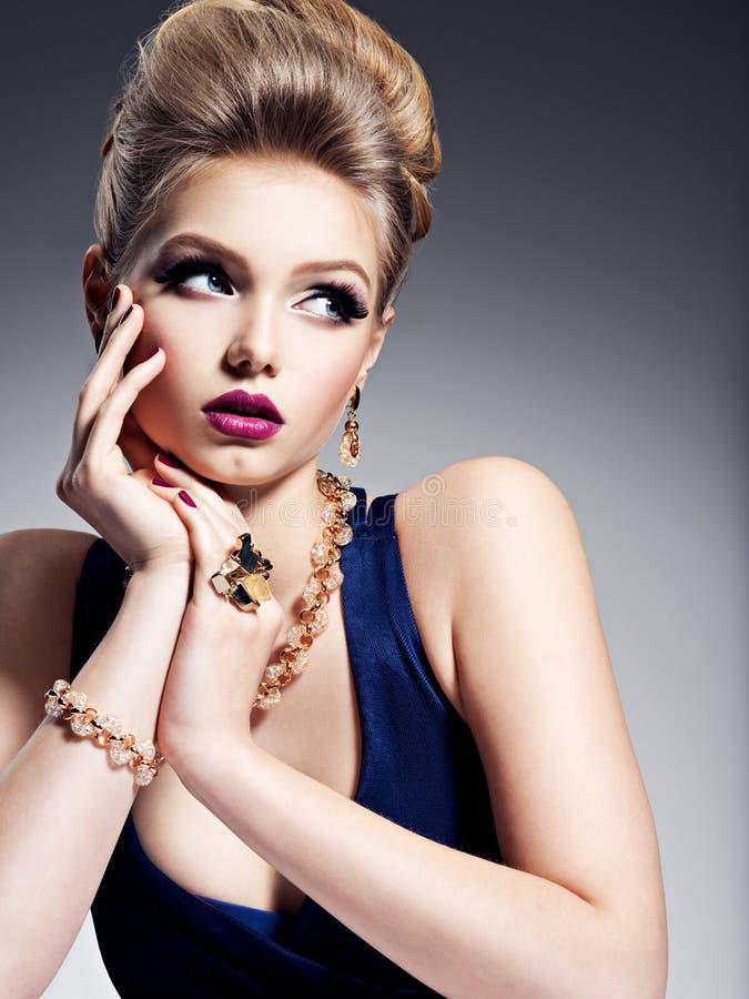 Милая девушка с красивыми ювелирными изделиями стиля причёсок и золота, ярким m стоковое изображение rf