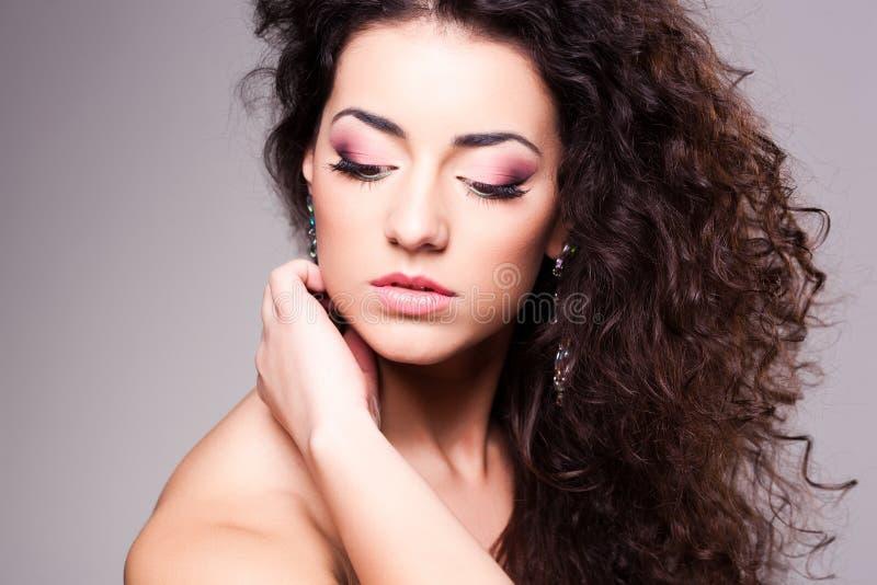 Милая девушка с составом курчавых волос нося - съемка студии стоковая фотография rf
