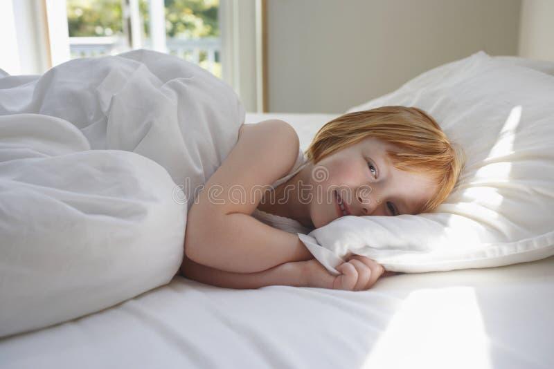 Милая девушка усмехаясь пока ослабляющ в кровати стоковое фото