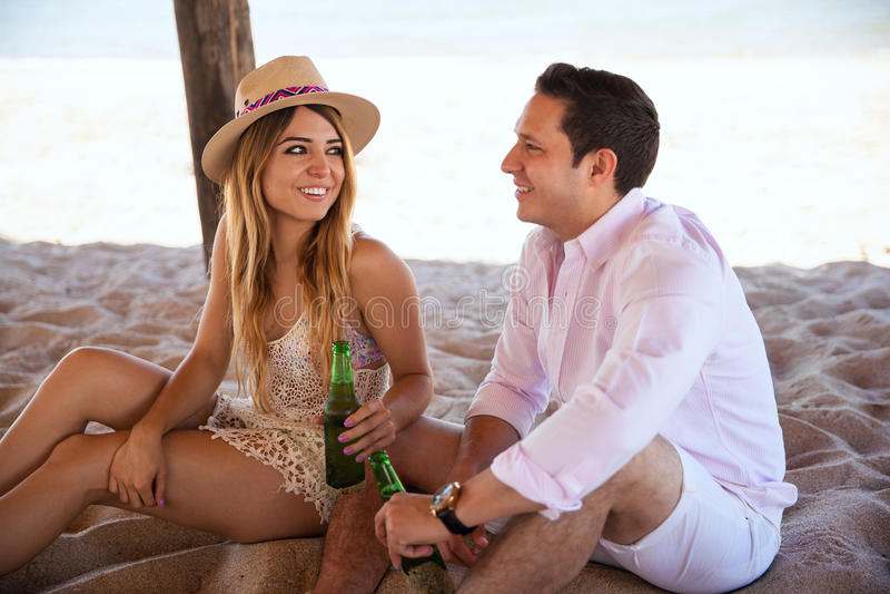 Милая девушка flirting с ее датой на пляже стоковое изображение rf