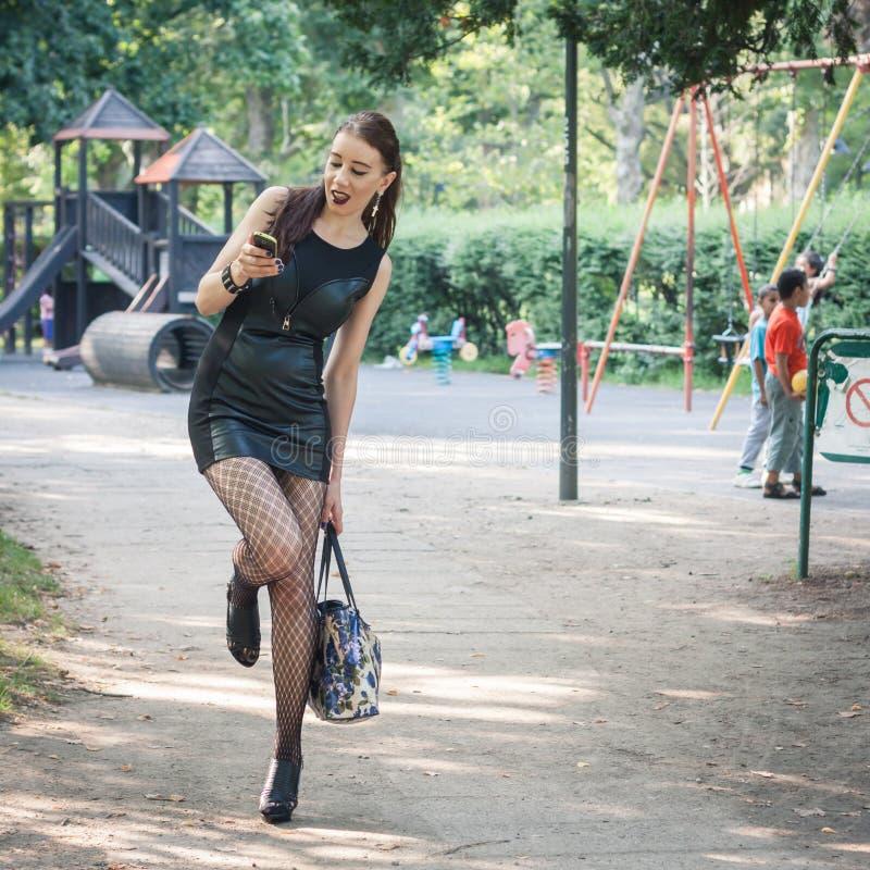 Милая девушка goth используя телефон в парке города стоковые изображения