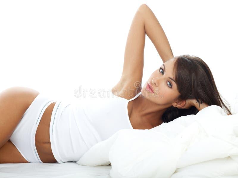 Милая женщина в белом нижнем белье лежа на ее стороне стоковые изображения rf