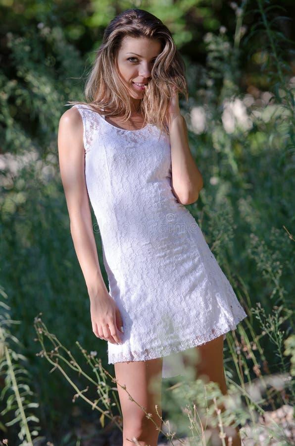Милая женщина в белом платье усмехаясь, красивые моменты в природе за зелеными цветами стоковая фотография rf