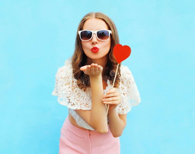 Милая женщина в солнечных очках с красным леденцом на палочке сердца посылает поцелуй воздуха над красочной синью стоковая фотография rf