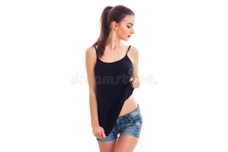 Милая женщина в черной футболке без бюстгальтера смотря в сторону стоковые изображения