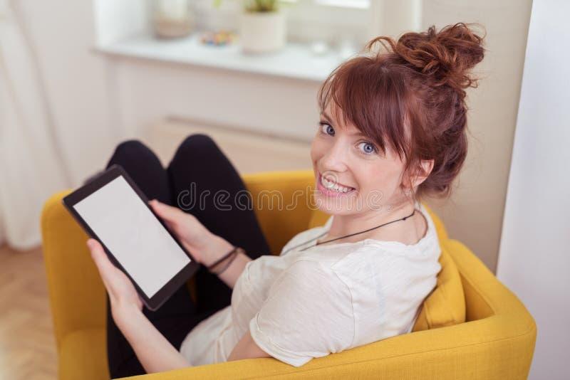 Милая женщина используя таблетку дома стоковая фотография rf