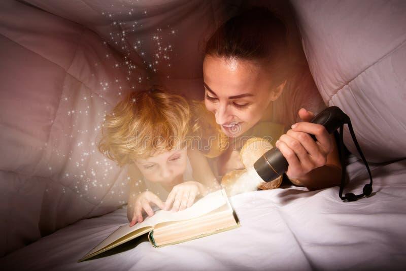 Милая женщина и ее сын читая книгу на ноче стоковые фотографии rf