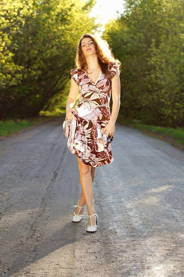 Download Милая женщина идя на дорогу Стоковое Изображение - изображение насчитывающей длиной, довольно: 33739147