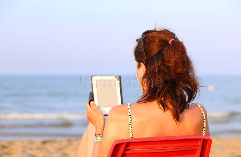 Милая женщина на красном стуле читает ebook на пляже в лете стоковое фото