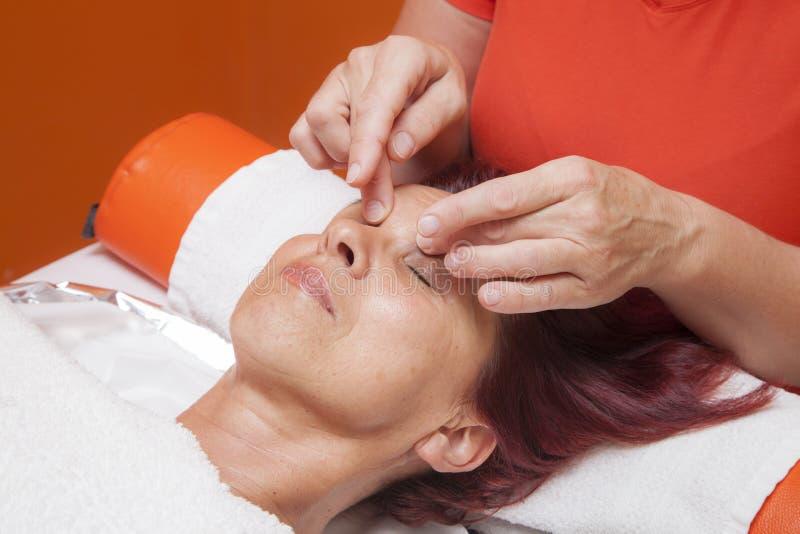 Милая женщина получает профессиональный лицевой массаж, лимфатический дренаж стоковые изображения rf