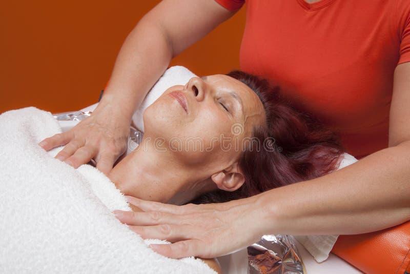 Милая женщина получает профессиональный лицевой массаж, лимфатический дренаж стоковая фотография