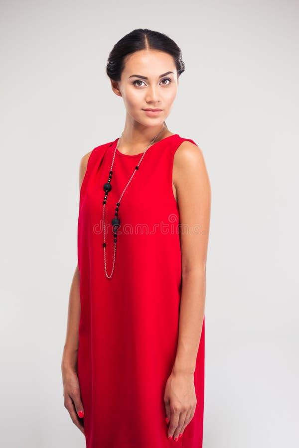 Милая женщина представляя в красном платье стоковая фотография