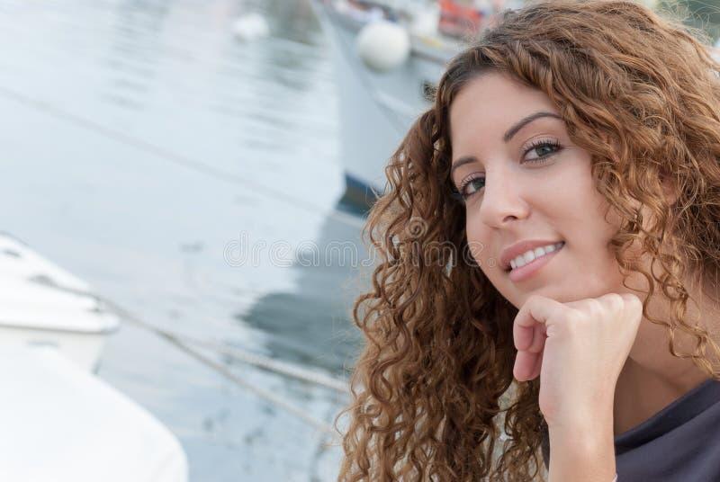 Милая женщина при вьющиеся волосы смотря на камеру стоковые изображения