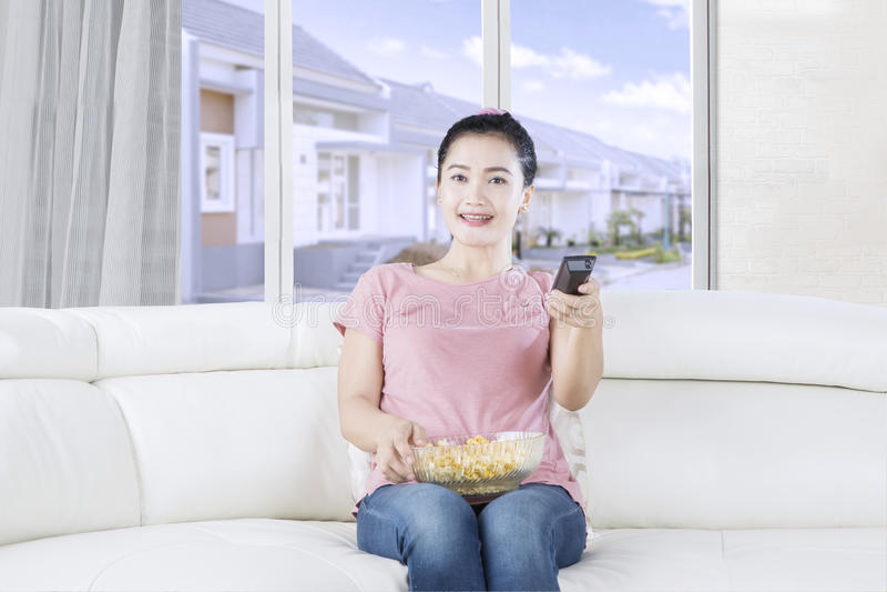 Милая женщина смотря ТВ на софе стоковая фотография rf