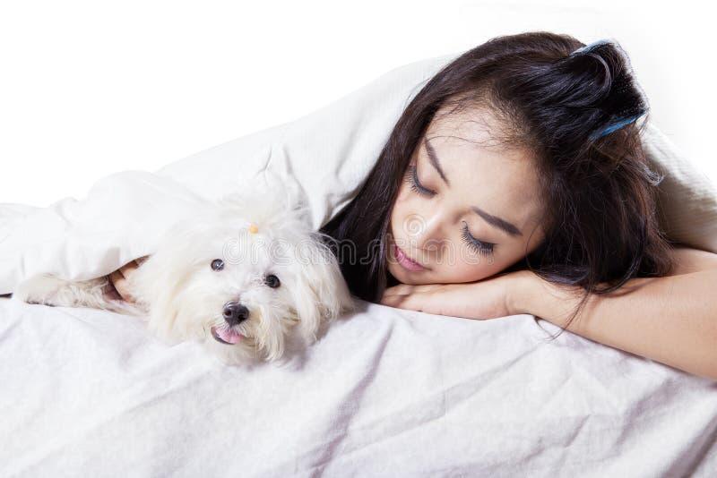Милая женщина спать с собакой на кровати стоковая фотография