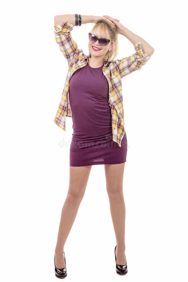 Милая женщина стоя в фиолетовом платье, изолированном на белизне стоковые фото