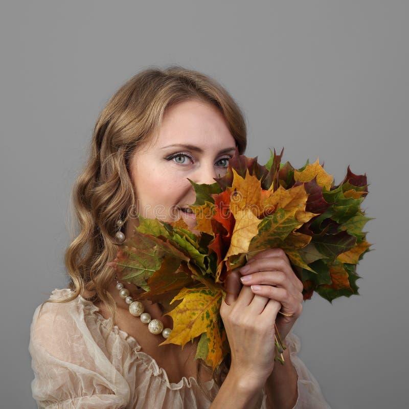 Милая женщина с листьями осени стоковые изображения rf