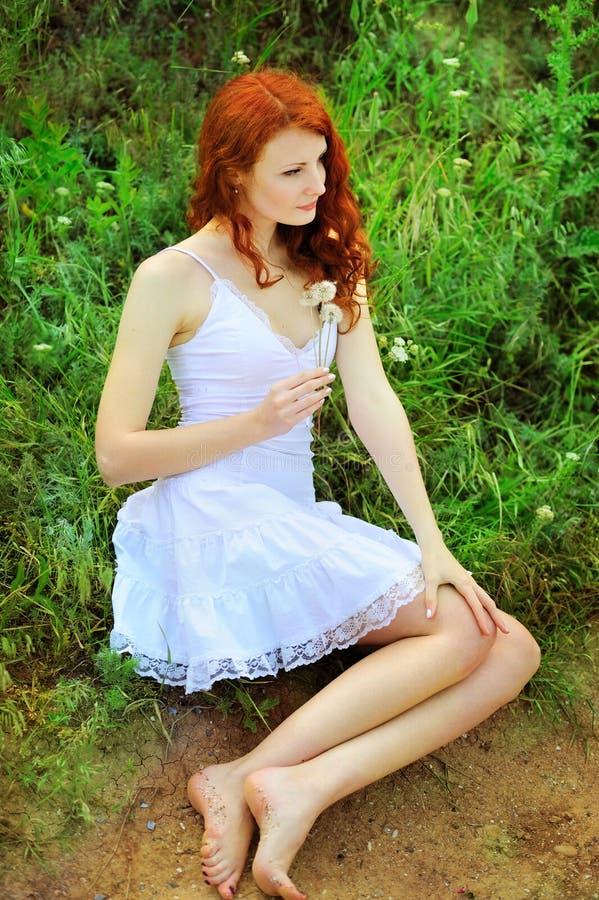 Милая женщина redhead с одуванчиками стоковое фото rf
