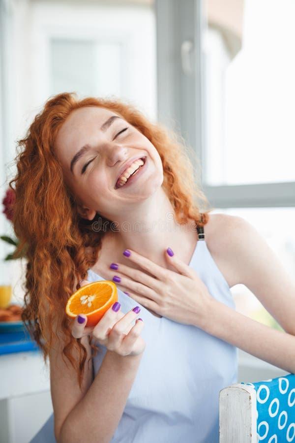 Милая жизнерадостная молодая дама redhead держа апельсин закрытые глаза стоковые фотографии rf