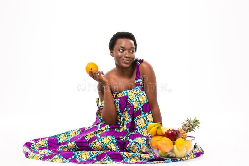 Милая задумчивая Афро-американская женщина сидя и держа апельсин стоковое фото rf