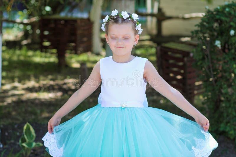 Милая малая девушка нося белое и голубое платье представляя над предпосылкой природы, ребенком с венком искусственных цветков на  стоковая фотография rf