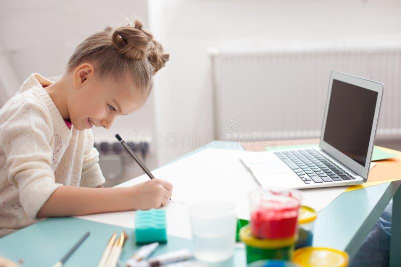 Милая малая девушка рисует с утехой стоковое фото