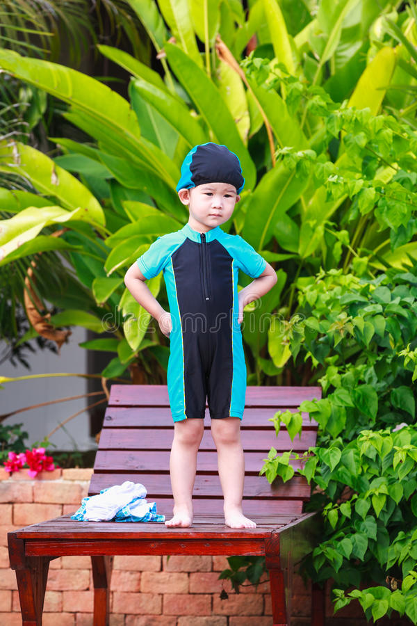 Милая маленькая азиатская девушка в купальнике стоя на расслабляющем стуле O стоковая фотография rf