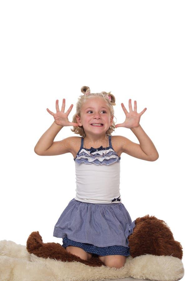 Милая маленькая белокурая девушка сидя на большой мягкой собаке стоковые фото