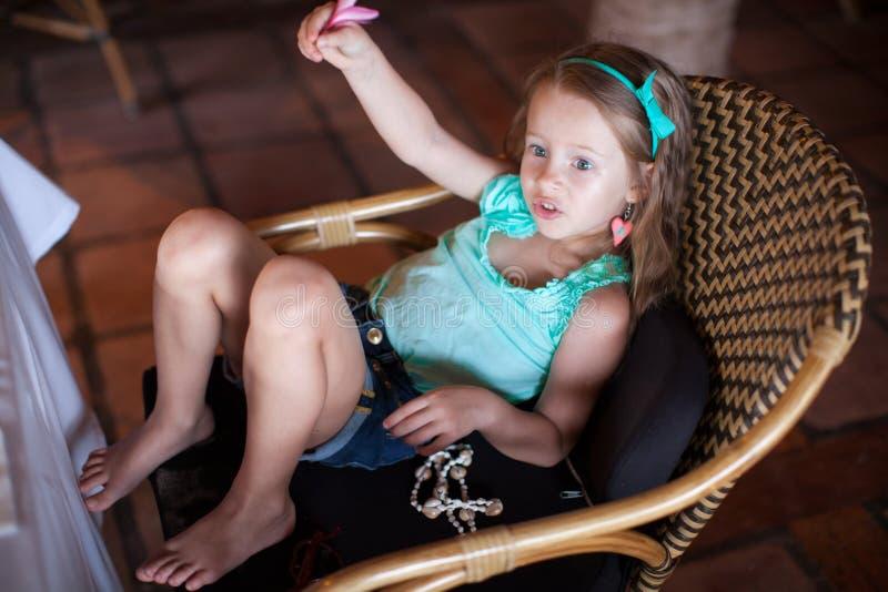 Милая маленькая девочка вызывая кельнера в ресторане стоковое фото rf