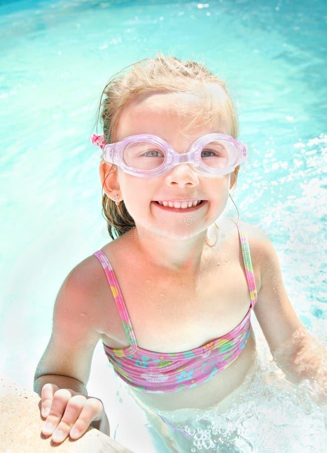 Милая маленькая девочка в бассейне в стеклах стоковое фото rf