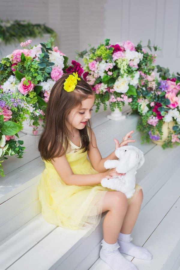 Милая маленькая девочка в желтом платье сидит и играет с игрушкой кролика в студии стоковое изображение