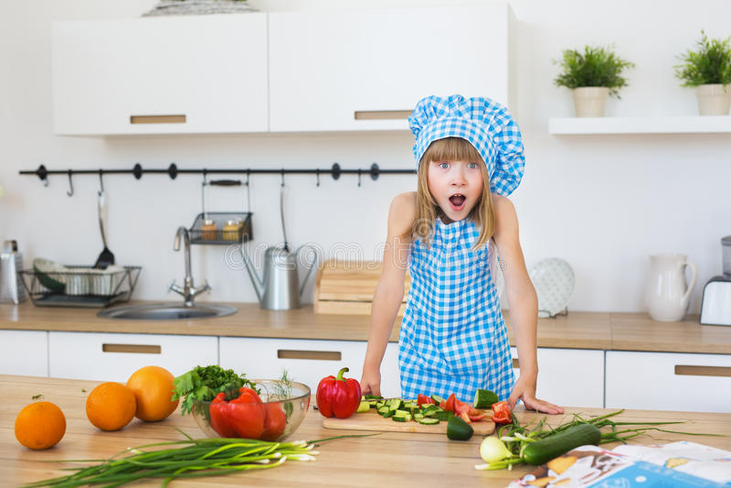 Милая маленькая девочка в одеждах кашевара раскрывает его глаза и рот на кухне стоковые изображения