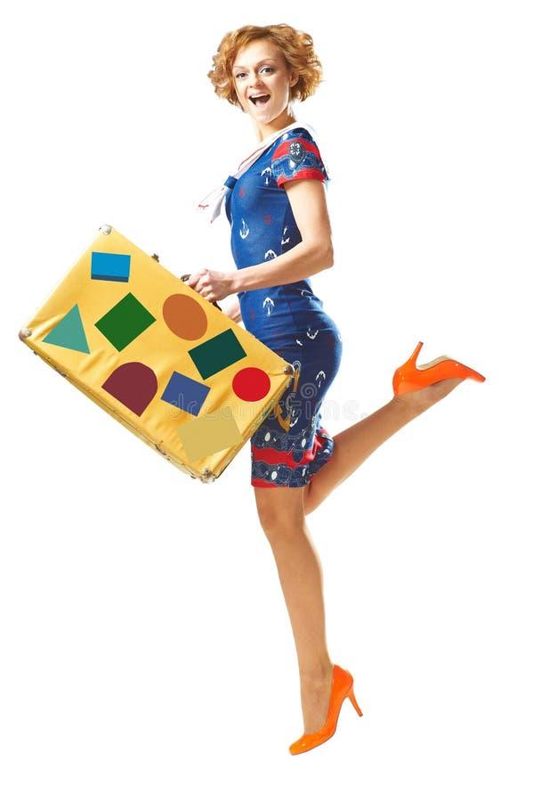 Милая маленькая девочка в скачке с чемоданом в руке стоковая фотография rf