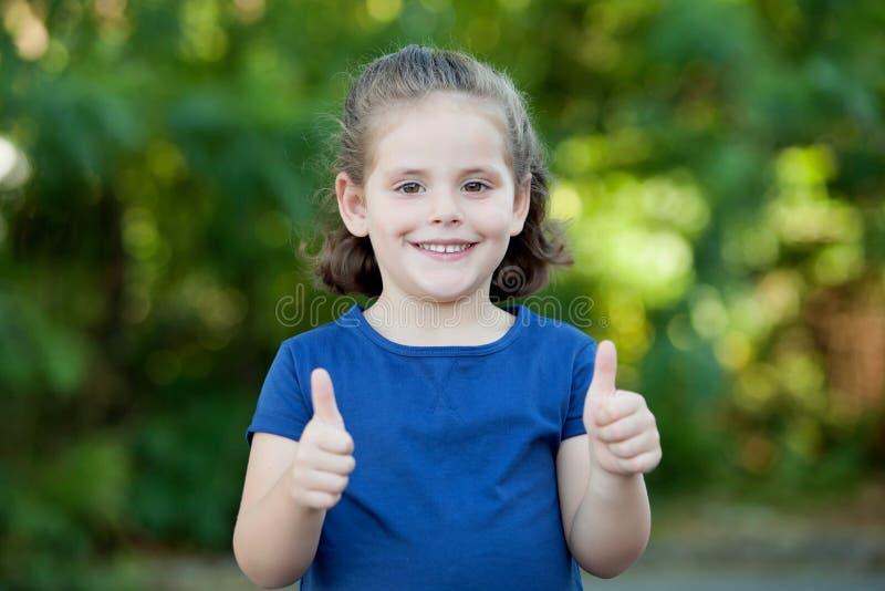 Милая маленькая девочка говоря о'кеы стоковое фото